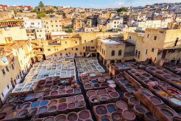 FES, MOROCCO - NOVEMBER 15, 2018:  Dye reservoirs in tannery in ancient medina Fes, Morocco, where the world famous moroccan leather is being made. Colored dye reservoirs and vats in a traditional tan