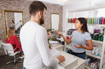 Man client talking with girl  assistant about services at salon