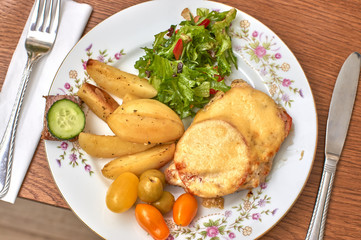 Baked meat with cheese and tomatoes on a plate with garnish and salad, top view
