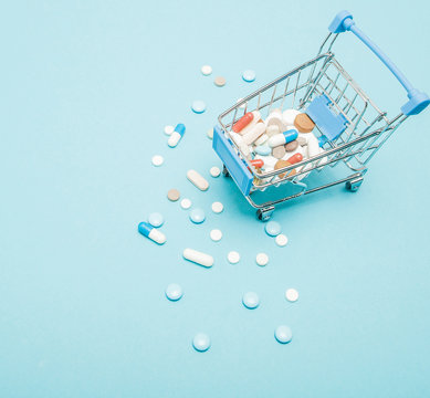 Pills and Shopping trolley on blue background. Creative idea for health care cost, drugstore, health insurance and pharmaceutical company business concept. Copy space