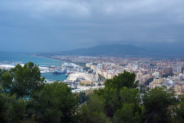 Malaga, Spain, February 2019. Panorama of the Spanish city of Malaga. Buildings, port, bay, ships and mountains against a cloudy sky. Dramatic sky over the city. Beautiful view.