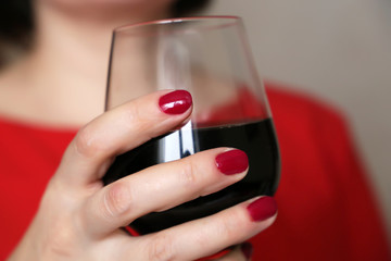 Woman drinking red wine, glass in female hands close up. Girl in red dress with manicured nails enjoying alcohol, concept of degustation, celebration, welcome reception