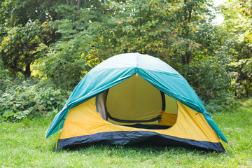 Tourism and adventures concept - nature landscape yellow camping tent with tree on green grass meadow
