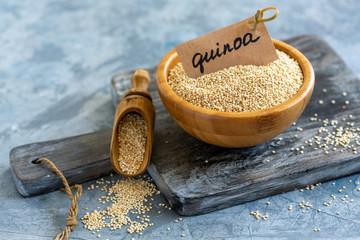 Raw white quinoa in a wooden bowl.