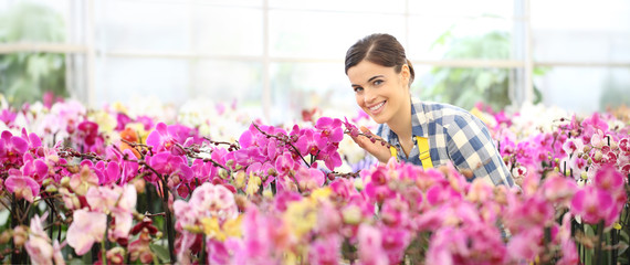 spring concept, smiling woman in the garden of orchids flowers