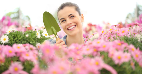smiling woman in garden of flowers with garden tools, spring concept