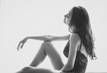 Sexy young woman in luxury underwear smoking a cigarette sitting in her room.  Black and white photo.