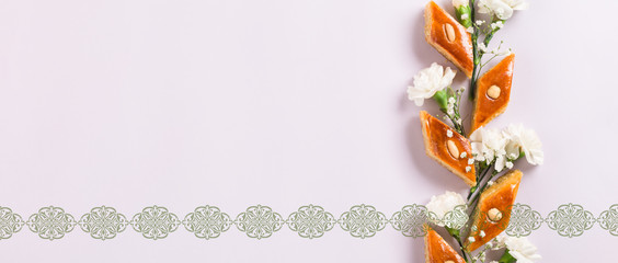 """Novruz floral composition of traditional Azerbaijan pastry pakhlava or baklava with beautiful white flowers spring greeting card, lilac background, text translation: """"Happy Nowruz"""", flat lay"""