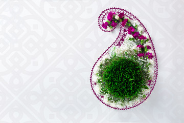 Novruz concept samani or semeni or sabzi for spring equinox March celebration in buta shape, paisley pattern motive, oriental style, nowruz or navruz background, copy space for text