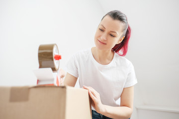 Young beautiful brunette girl in a white t-shirt packs cardboard boxes with a dispenser and adhesive scotch adhesive tape. The concept of moving to a new home.