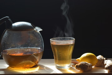 ginger tea in a tea pot and glass on a wooden board on a black background