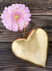 Golden heart and pink flower against wooden background