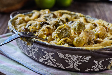 Foto op Canvas Brussel Delicious and healthy brussels sprouts baked in cream sauce with cheese and bread crumbs on a wooden table next to fork ready to eat