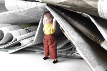 Mini Human Figure of Man or Child Holding Heap of Newspapers