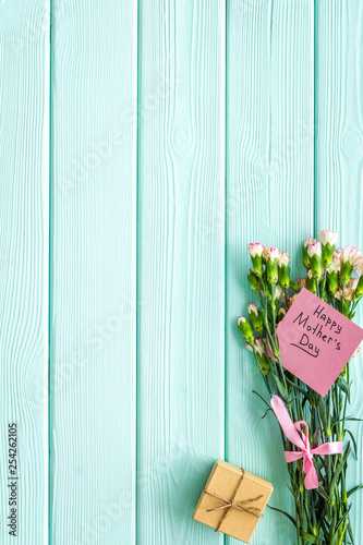Mother's Day congratulations. Carnations and gift box on blue turquoise wooden background top view copy space