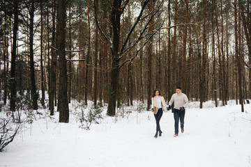 Winter love story on ice. Stylish guy and girl with walk in snowy forest. Romance