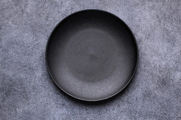 Empty black plate on gray background. Top view, with copy space
