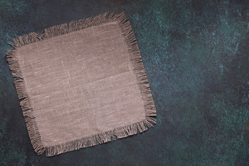 Taupe napkin on dark grunge table top view with copy space