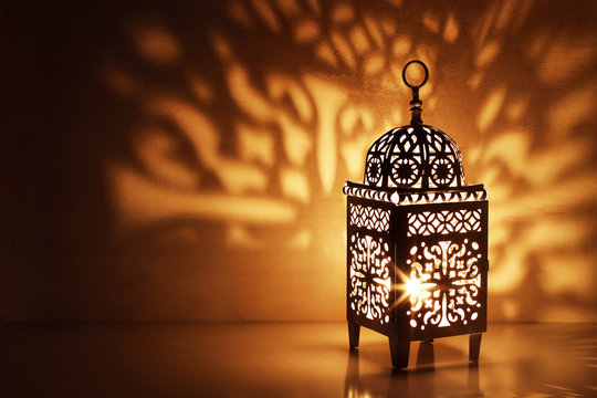 Silhouette of Moroccan ornamental lantern with burning glowing candle. Decorative shadows. Festive greeting card, invitation for Muslim holy month Ramadan Kareem. Festive night background.