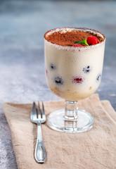 Tiramisu dessert in glass with cocoa powder and berries