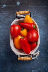 Basket with fresh red and yellow tomato and peppers on grunge table above