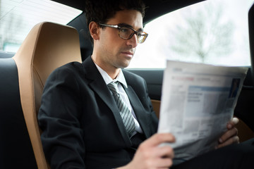 Young manager reading a newspaper in the back seat of a car
