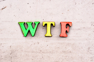 Inscription wtf What is Terrible Failure, Internet Slang, COLORED abbreviation in wooden letters on a light background