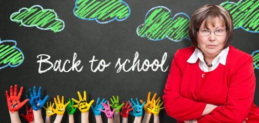 """Lehrerin vor Wandtafel mit Aufschrift """"Back to school"""""""