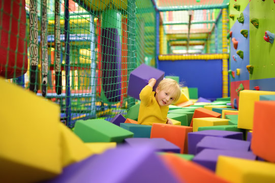 Cute little boy plays with soft cubes in the dry pool in play center. Kid playing on indoor playground in foam rubber pit in trampoline.