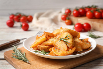 Plate with tasty baked potatoes and rosemary on wooden board