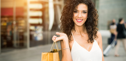 Beautiful woman holding a bag in a shopping mall