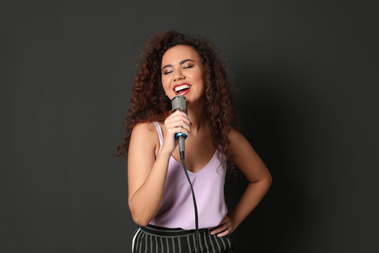 Curly African-American woman in stylish clothes singing with microphone on black background
