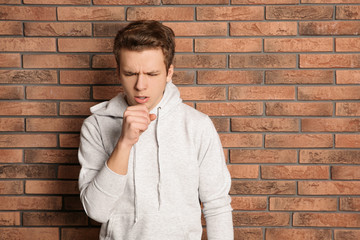 Teenage boy suffering from cough near brick wall. Space for text