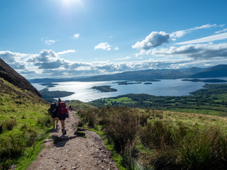 two girls hiking with beautiful lake (loch lomond) and green landscape