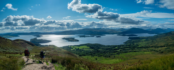 panorama of two girls hiking with beautiful lake (loch lomond) and green landscape