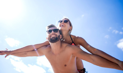 Man carrying woman piggyback on beach.