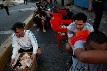 Men sit on the street after being detained while looting during an ongoing blackout in Caracas
