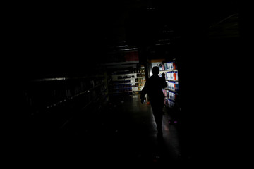 A worker inspects damage in a supermarket after it was looted during an ongoing blackout in Caracas