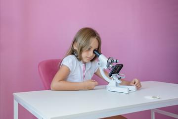 Criança menina pesquisando e estudando no microscopio