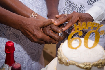 Hands cutting cake