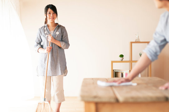 ほうきで掃除をする女性とテーブルを拭く男性