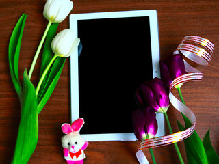 Flat lay photo with white and purple tulips and tablet computer with black mockup screen. Greeting card for Mother's Day, Women's Day or Easter