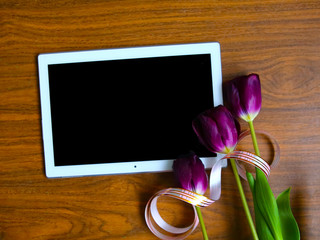 Flat lay photo with purple tulips and tablet computer with black screen. 8 March or Easter greeting card