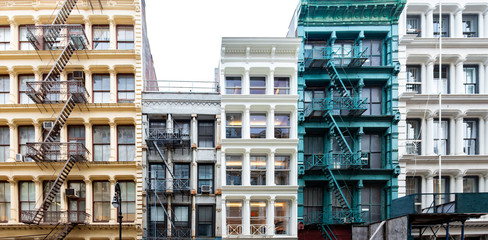 Exterior view of a block of colorful old historic buildings along Greene Street in the SoHo neighborhood in New York City with pattern of windows and fire escapes