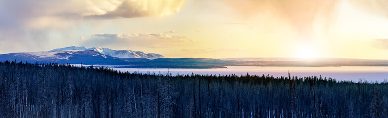 Panoramic frozen winter landscape view of Yellowstone National Park with sunlight shining in the background of the snowy mountain range