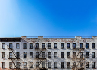 Old white brick apartment building with windows and fire escapes and an empty blue sky background overhead in New York City