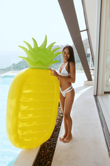 Summer fun. Woman in swimsuit near pool with pineapple float