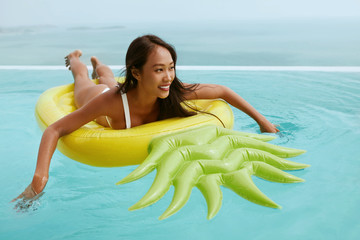 Summer vacation. Happy woman relaxing in swimming pool on float