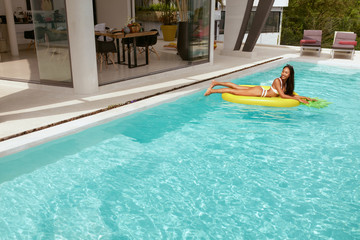 Summer vacation. Woman sunbathing on float in swimming pool