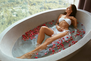 Woman in spa taking bath with flowers. Girl relaxing in bath tub